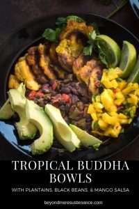 Tropical Buddha Bowls with mango salsa, black beans, fried plantains, and avocados in a black ceramic bowl.