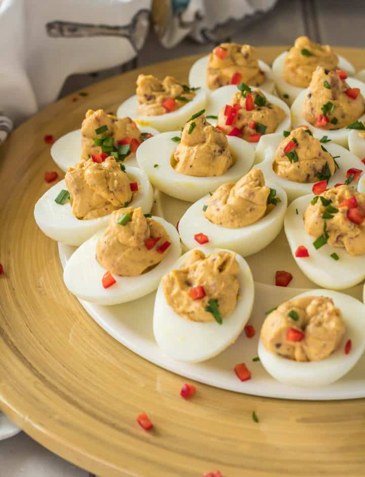 Maple Bacon Deviled Eggs close up on a yellow bamboo platter with a print tea towel.