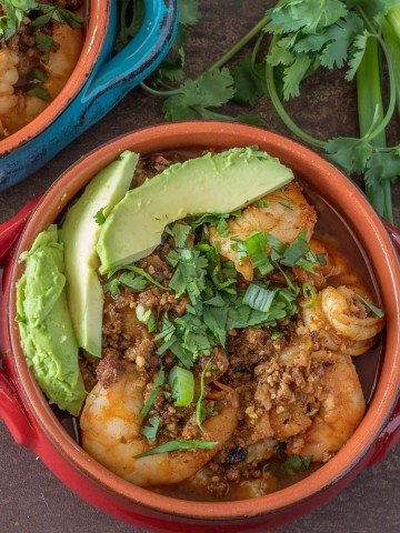 Gluten free healthy Mexican shrimp and grits in a red stoneware bowl with avocado and cilantro.