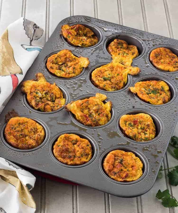 Mexican Mini-Frittatas with Chorizo and Cotija in an aluminum muffin pan.