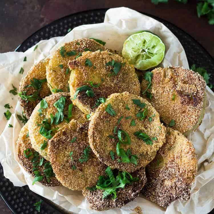 A close up bird's eye view of 10 slices of Mexican fried green tomatoes garnished with scallions and cilantro with a lime half.