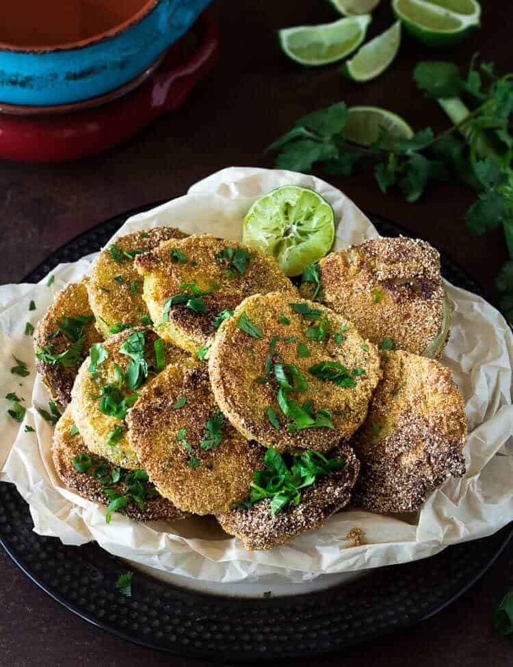 Mexican Fried Green Tomatoes on parchment with lime and cilantro.