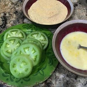 Sliced fried green tomatoes, cornmeal and spices, and buttermilk/egg mixture prior to cooking.