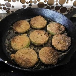 The fried green tomatoes in a black cast iron skillet.