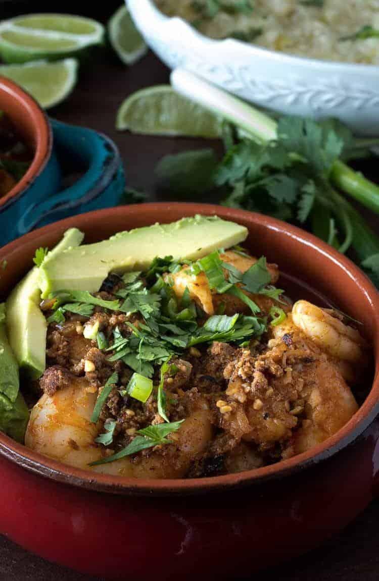 Healthy Mexican Shrimp and Grits topped with avocado and cilantro in a red stoneware bowl close up.