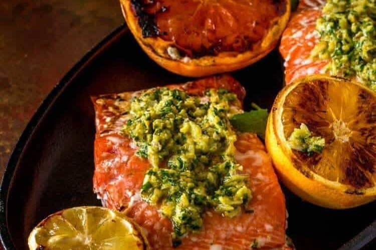 Citrus Gremolata with Grilled Salmon on a cast iron platter with grilled citrus garnish.