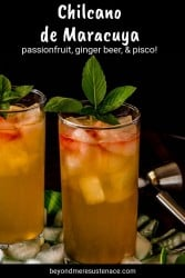 A new pin for a passionfruit chilcano in 2 highball glasses on a green tray with fresh mint sprig.