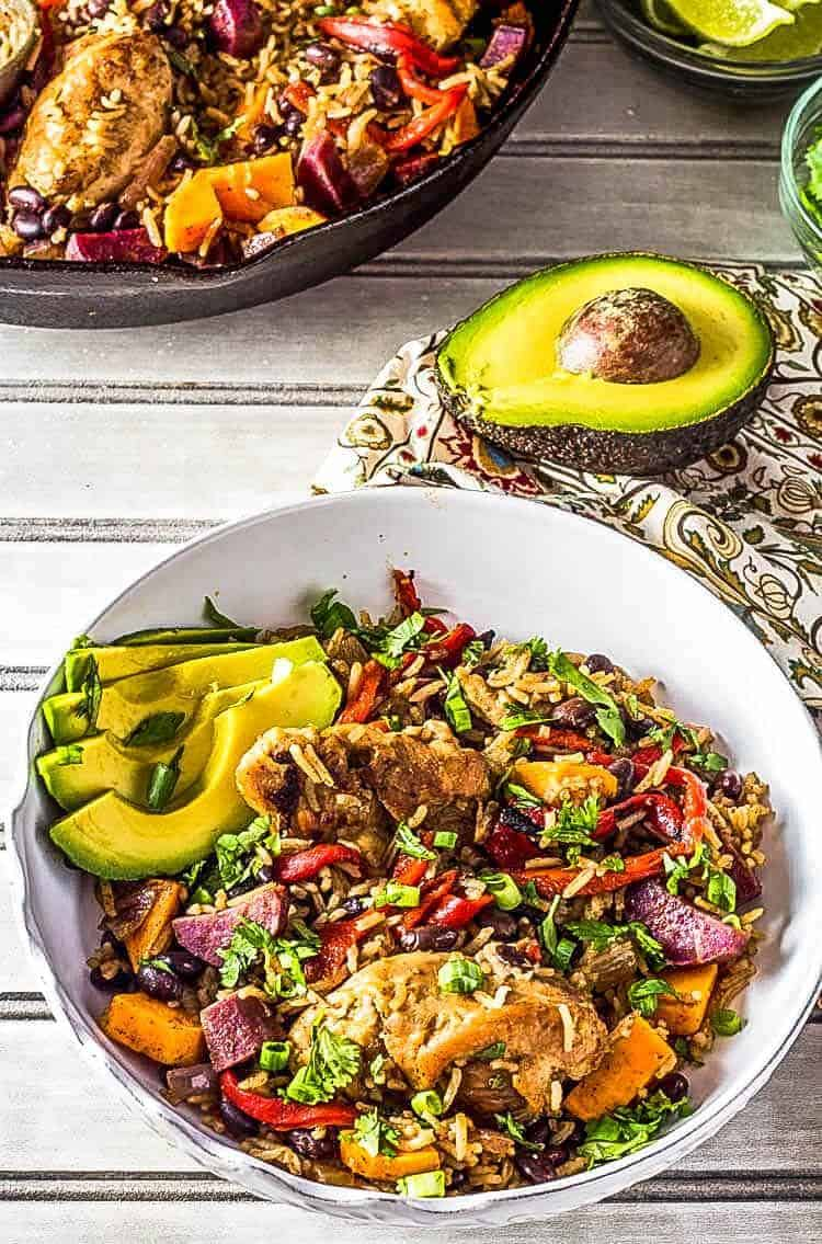 Caribbean Arroz con Pollo - Chicken, rice, and vegetables in a white bowl with avocado.