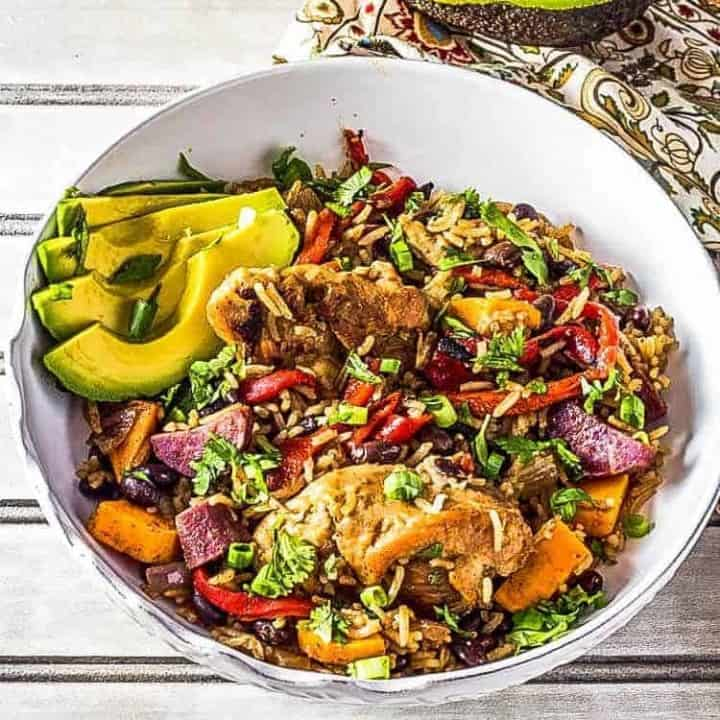 Caribbean Arroz con Pollo - Chicken and Rice close up in a white bowl.