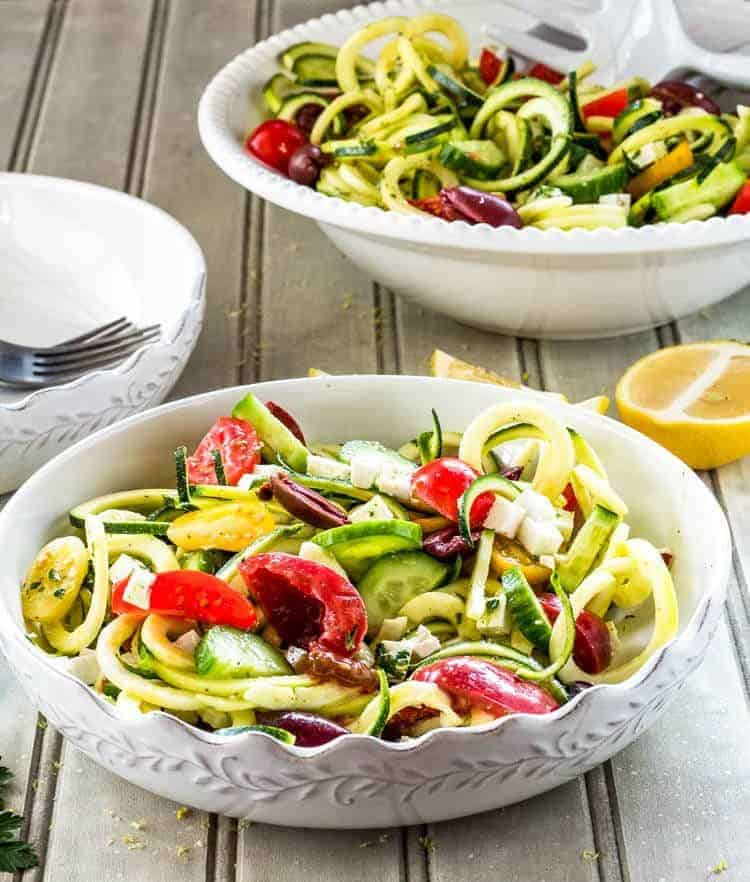 Greek Zoodle Salad served in a white scalloped edge ceramic bowl with lemon wedge.