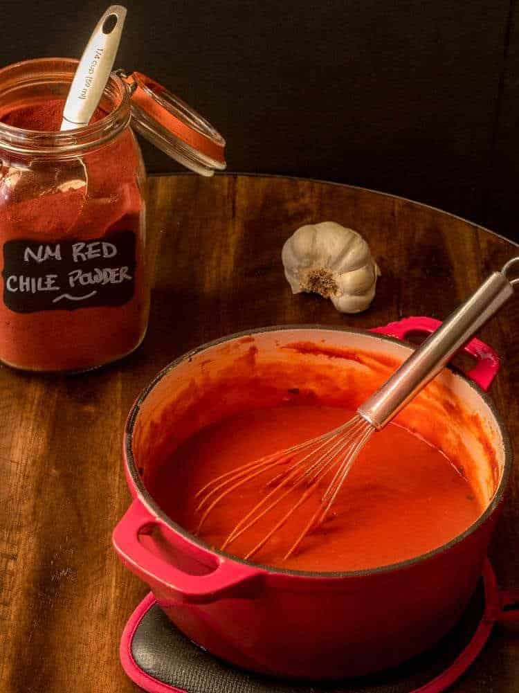 New Mexico Gluten-Free Red Chile Sauce in a red cast iron Dutch oven with a glass jar of NM red chile powder.