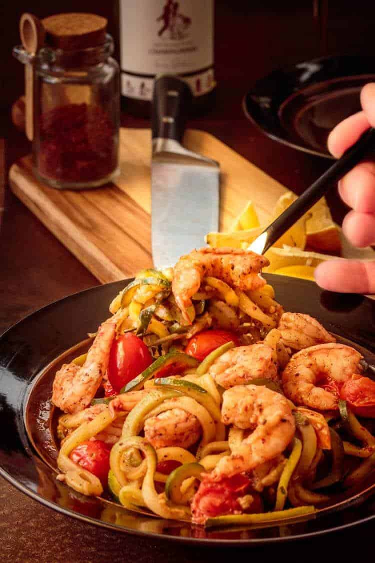 15 Minute Shrimp Zoodles Turkish Style  - a fork in a bowl of shrimp zoodles.