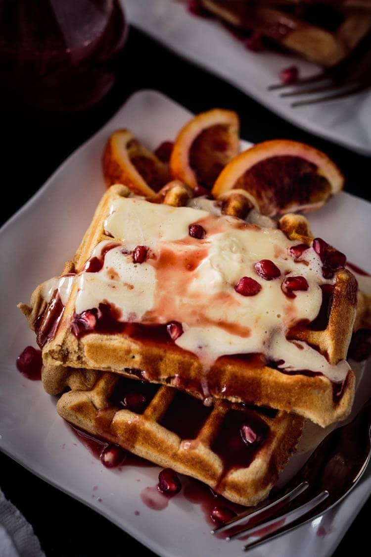 A close up of bacon waffles with pomegranate blood orange syrup and orange mascarpone cream on a square white plate with blood orange wedges.