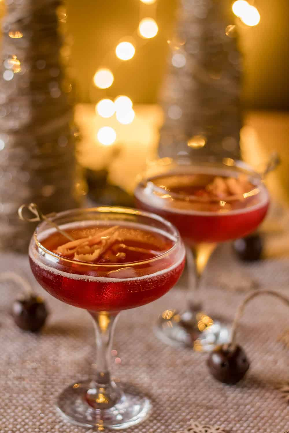 2 Mexican Manhattans on burlap with Christmas ornaments and twinkly lights.