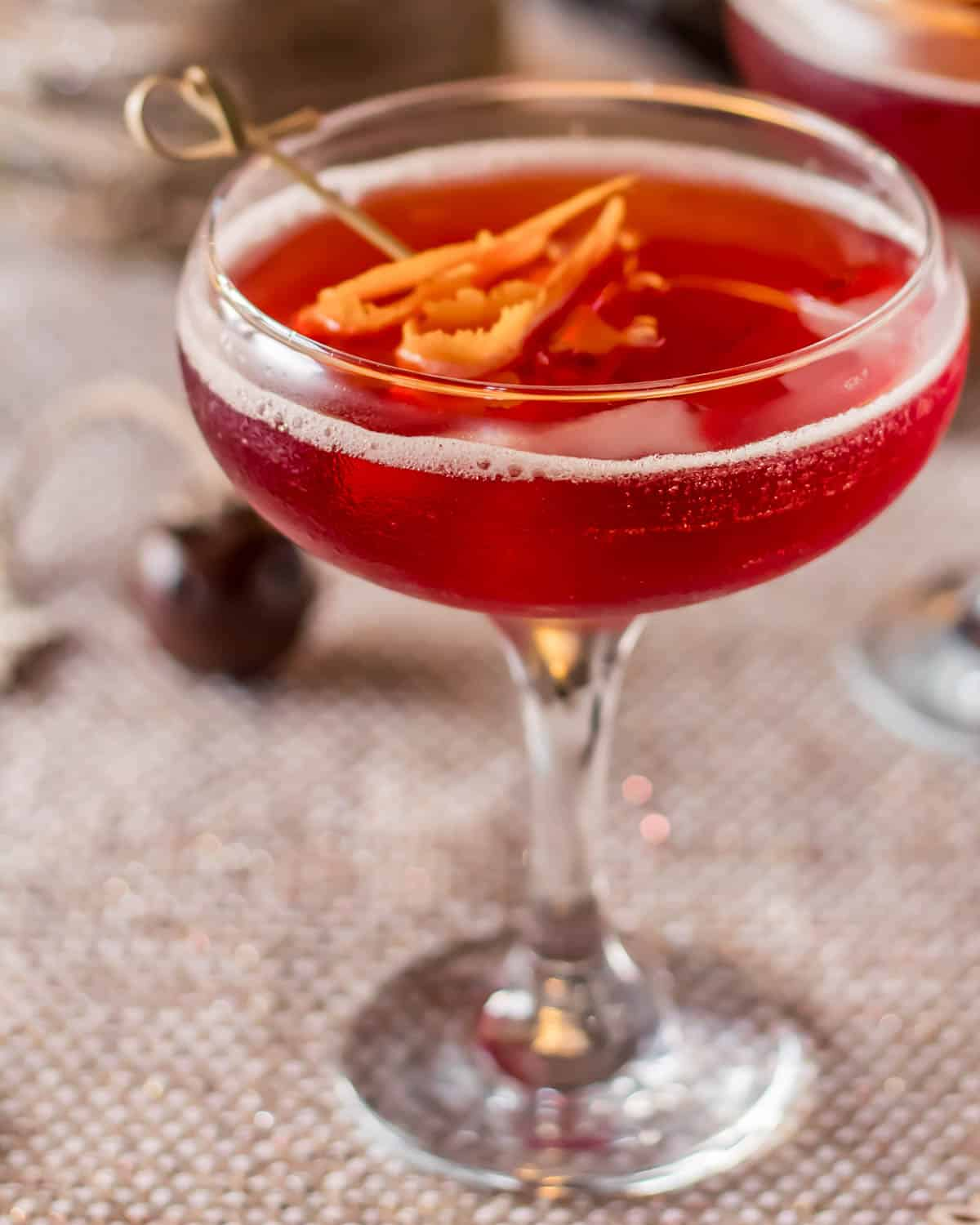 A close up of a coupe glass with a Mexican Manhattan garnished with an orange twist.