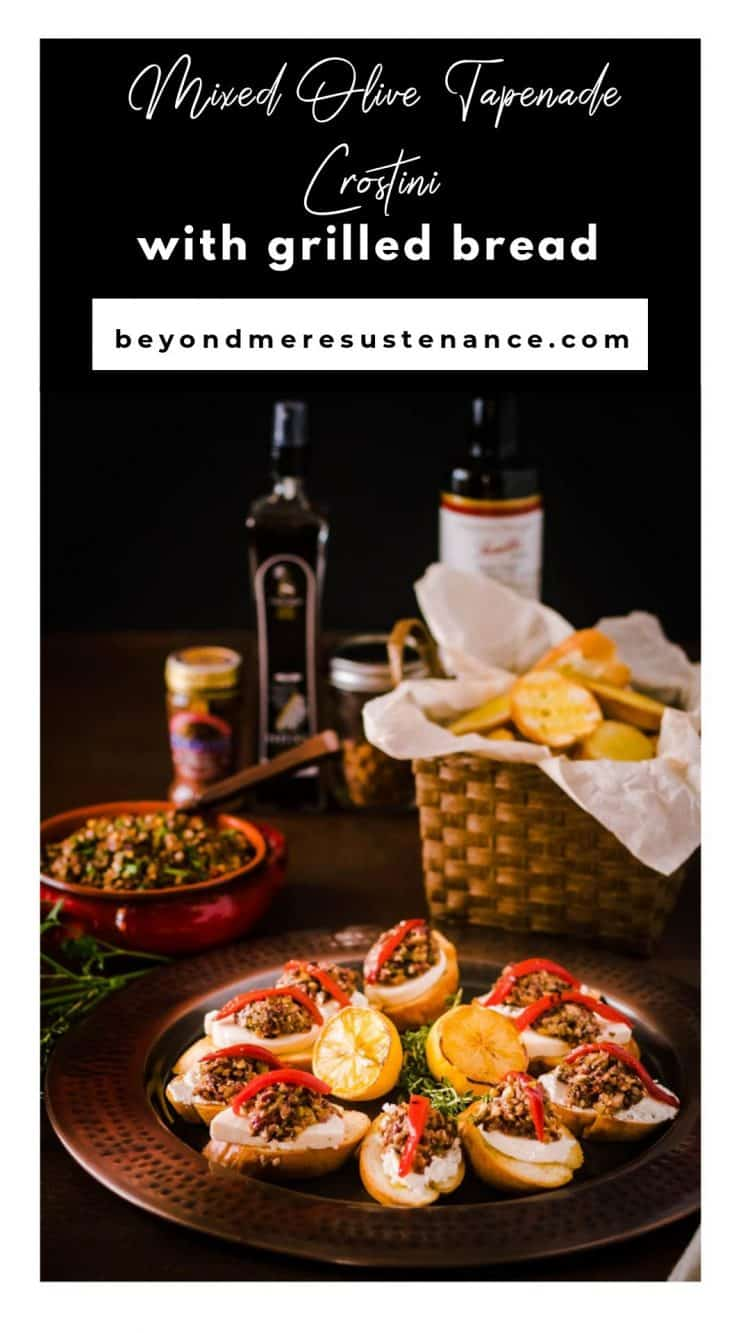 A copper plate with olive tapenade crostini, a basket of grilled bread, a crock of prepared tapenade.