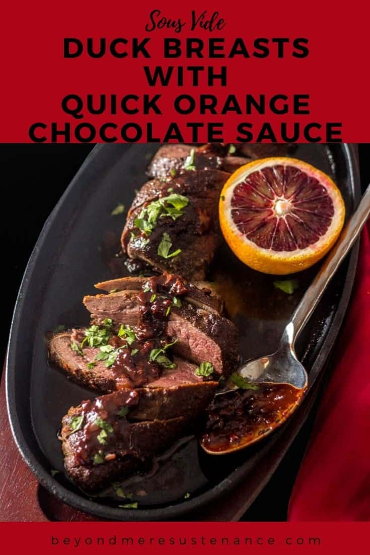 Sous Vide Duck Breasts with Quick Orange Chocolate Sauce garnished on a serving plate with a spoon on a red tablecloth.