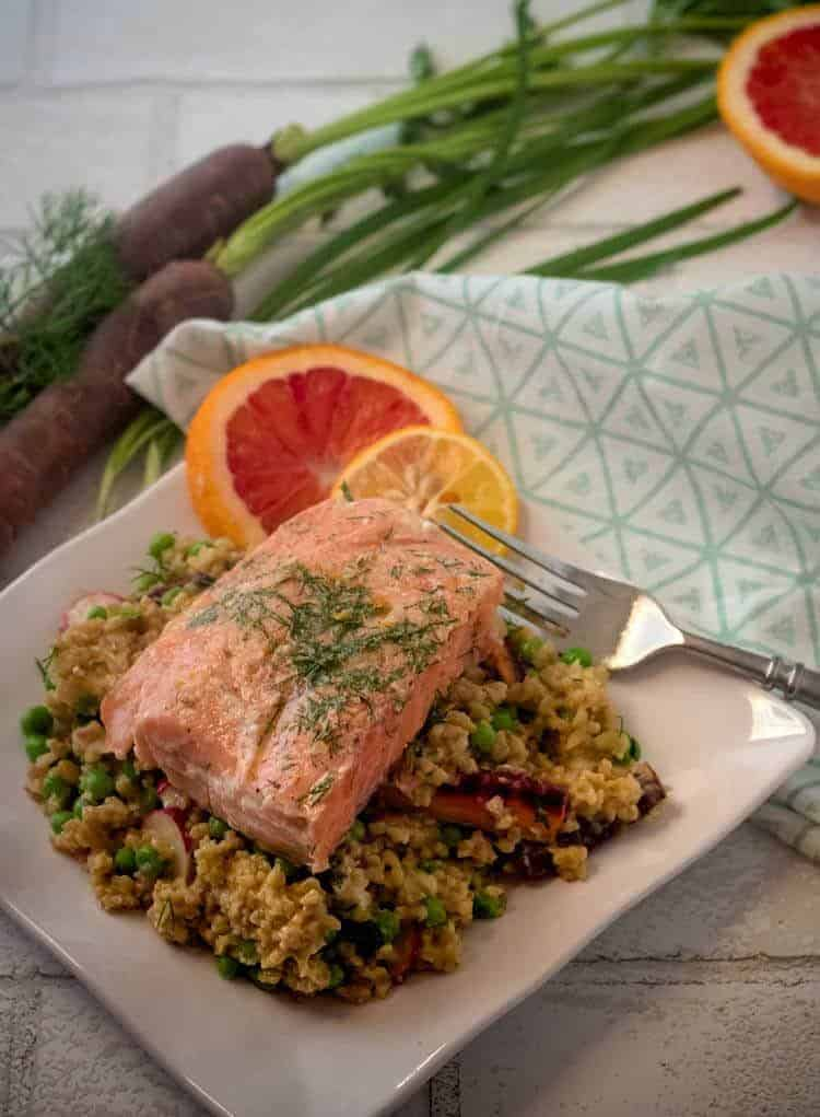 Spring Vegetable Freekeh Salad on a white plate with Salmon and a print napkin.