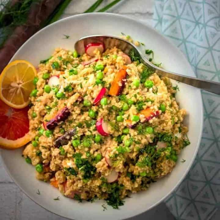 Spring Vegetable Freekeh Salad in a white bowl with serving spoon and cloth napkin.