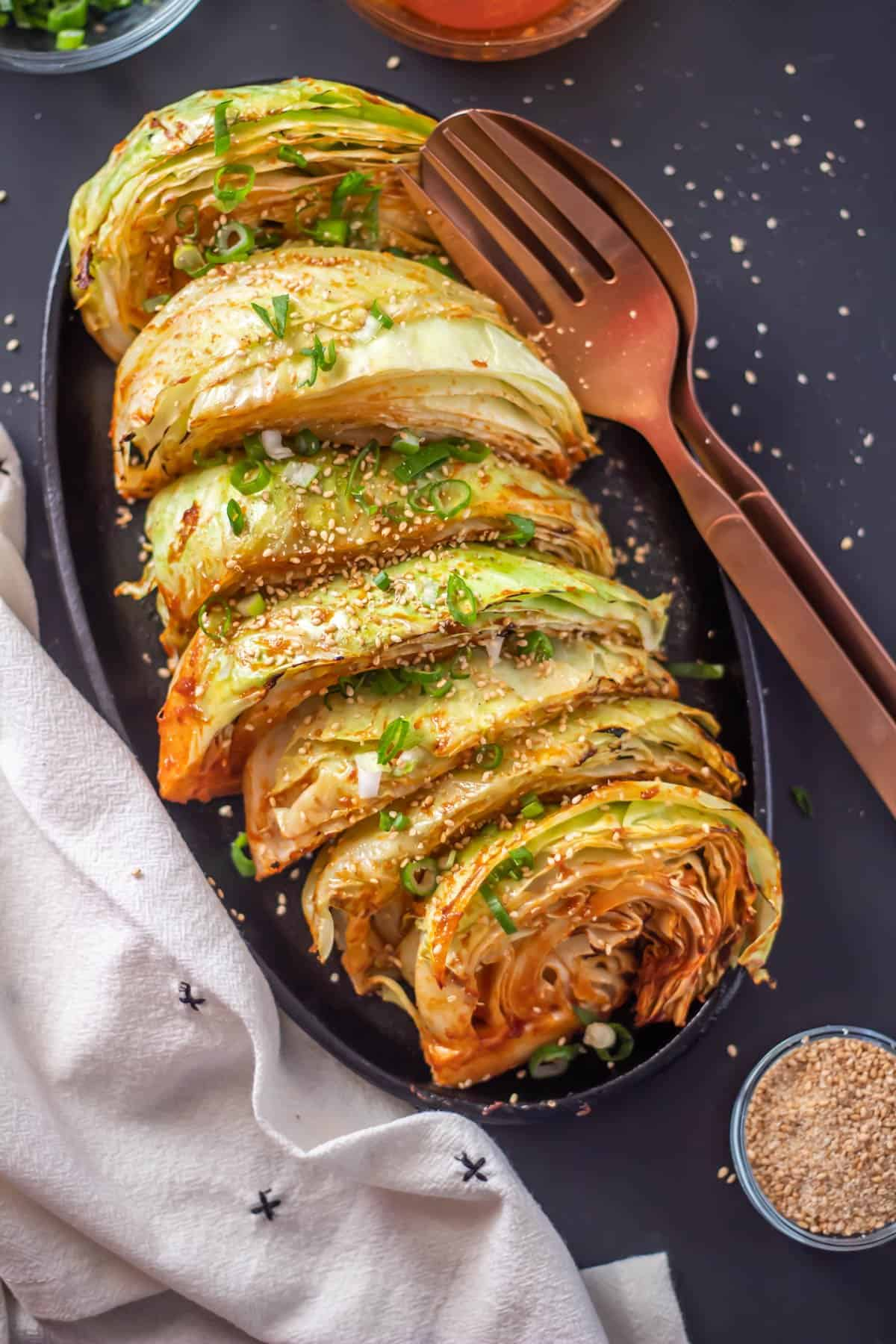 Grilled Cabbage Wedges with a Korean Glaze on an oval cast iron pan with copper serving utensils and extra gluten free and vegan gochujang sauce.