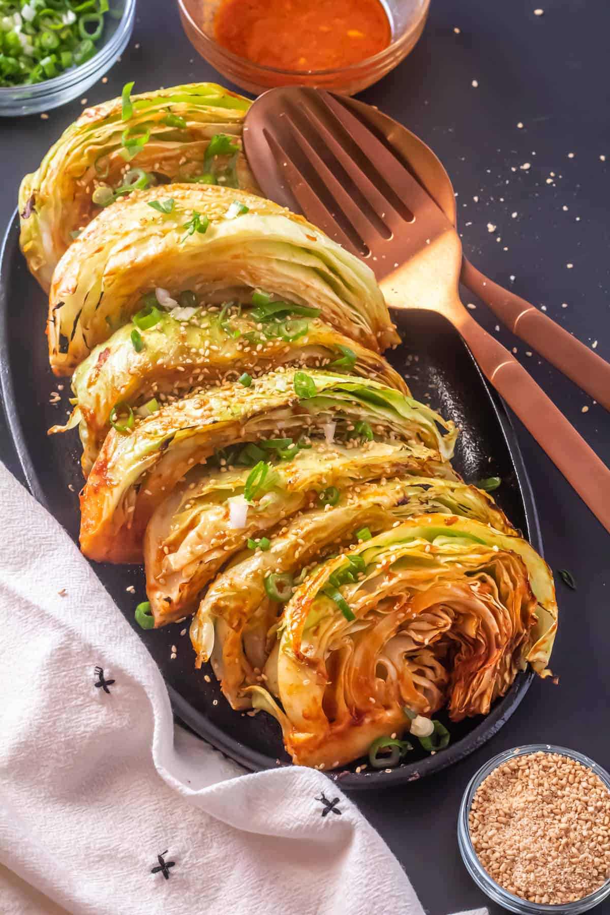 Grilled Cabbage Wedges with a Korean Glaze Close Up with a beige napkins and garnishes.
