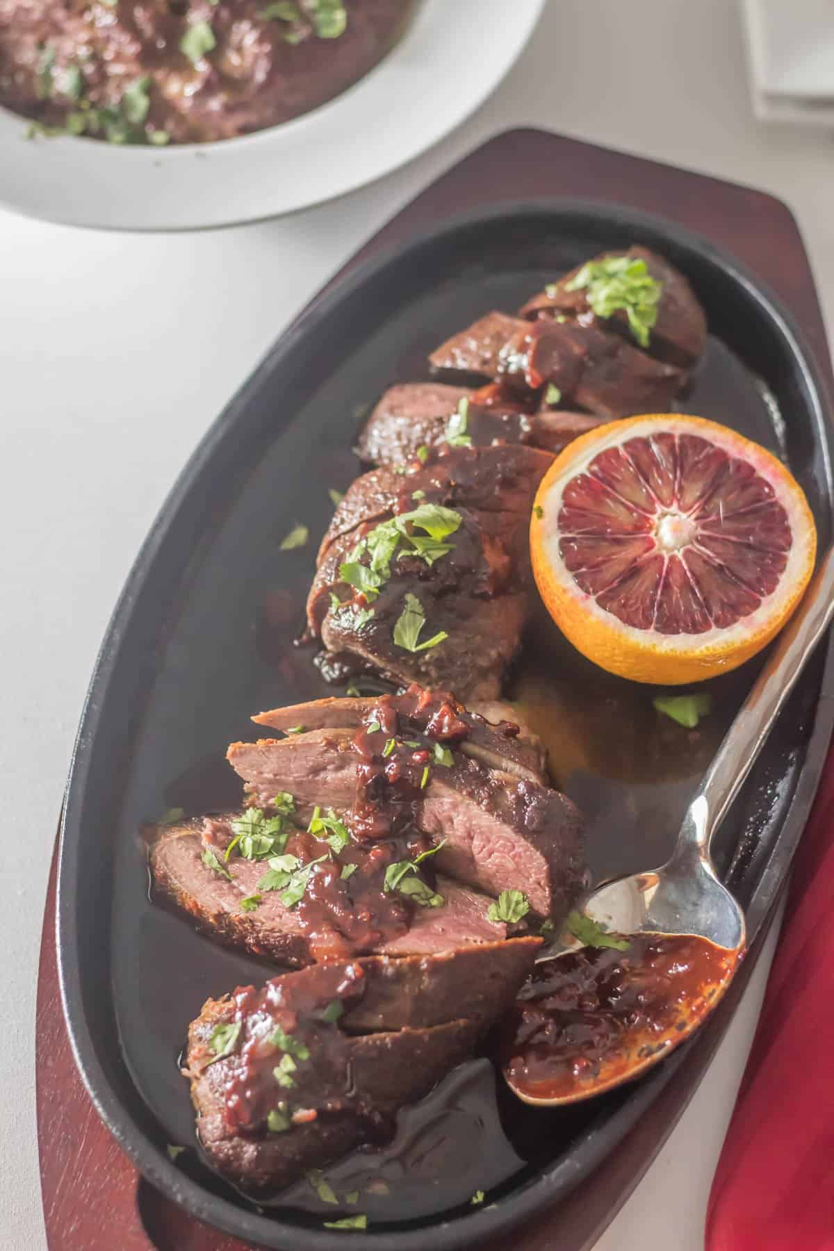 Sous Vide Duck Breasts with Quick Orange Chocolate Sauce on an oval cast iron server with half of a blood orange and cilantro garnish.