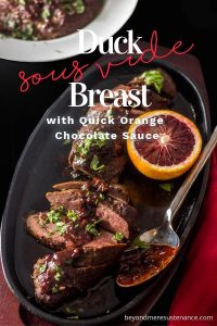 Sous Vide Duck Breasts with Blood Orange Chocolate Sauce on a cast iron serving dish with half a blood orange and a silver spoon.