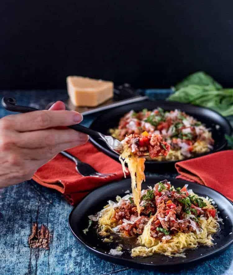 Spaghetti Squash with Easy Sausage Marinara - My hand with a fork full of spaghetti squash and marinara sauce.