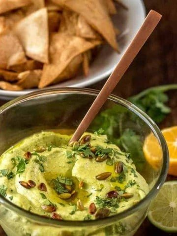 Mexican-Inspired Hummus with Avocado in a clear glass bowl with baked chips.