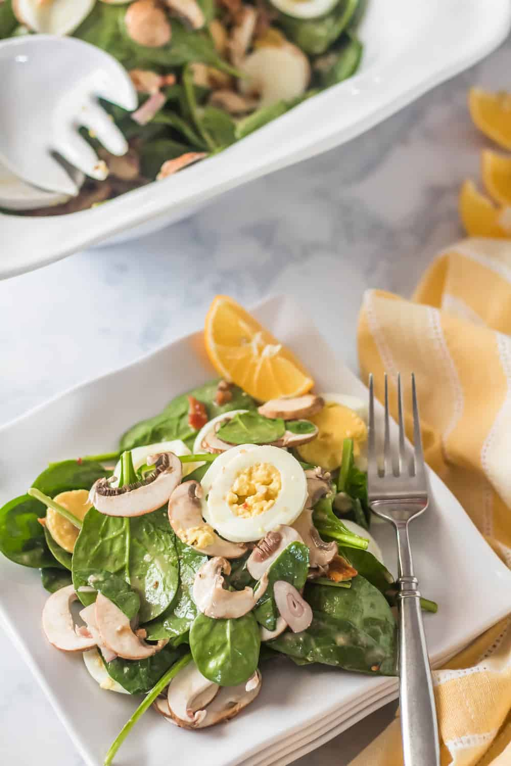 Classic Spinach Salad with Honey Dijon Vinaigrette - An individual plate of spinach salad with a fork.