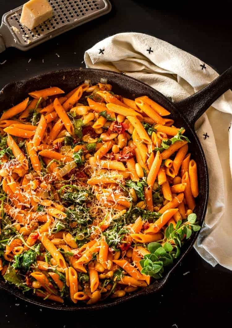 Instant Pot Cannelini Beans with Penne, Arugula, and Slow Roasted Tomatoes in a cast iron skillet.