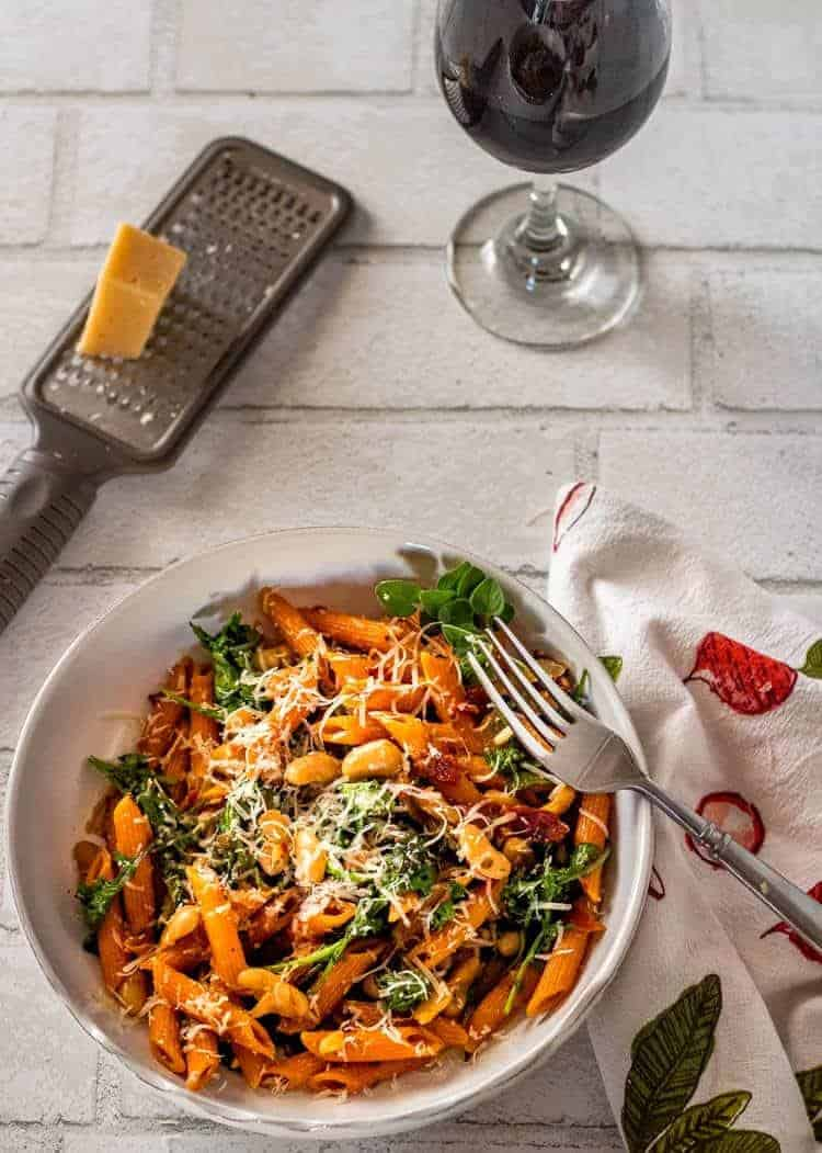 Instant Pot Cannelini Beans with Penne, Arugula, and Slow Roasted Tomatoes - plated bowl of pasta with fork and wine glass.