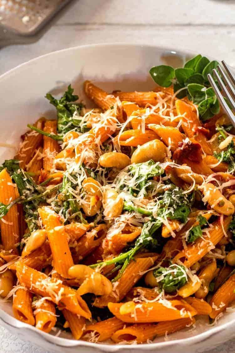 Instant Pot Cannelini Beans with Penne, Arugula, and Slow Roasted Tomatoes - close up of pasta in a bowl.