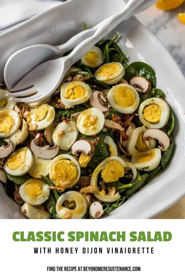 A Classic Spinach Salad with Honey Dijon Vinaigrette in a square white bowl with salad tongs.