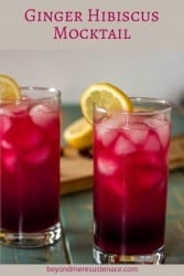Ginger Hibiscus Mocktail in 2 high ball glasses with lemon twist.