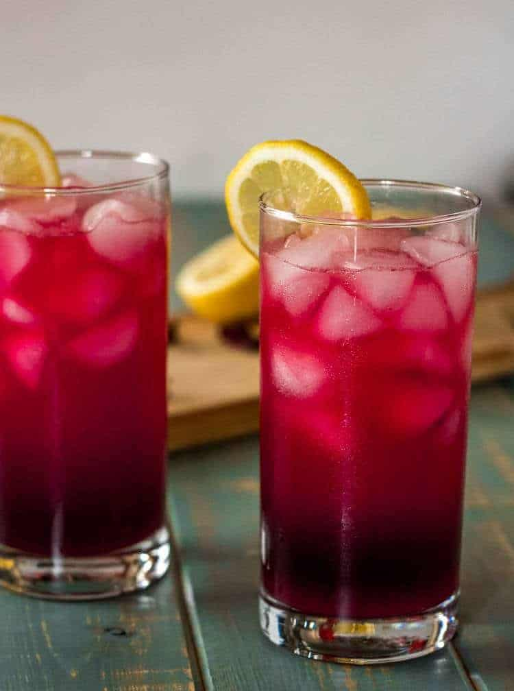 Ginger Hibiscus Martini - 2 ginger hibiscus mocktails in highball glasses with lemon wheels...