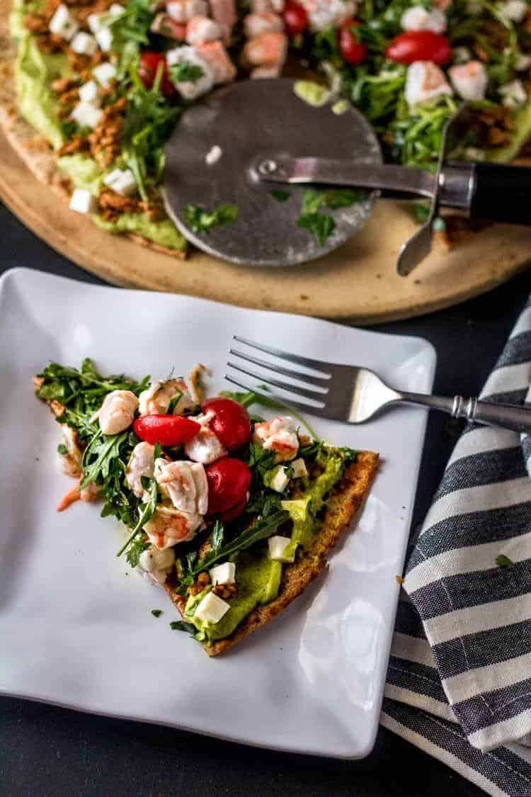 Mexican Grilled Pizza with Shrimp Ceviche and Avocado Hummus - a slice of shrimp ceviche flatbread on a square white plate.