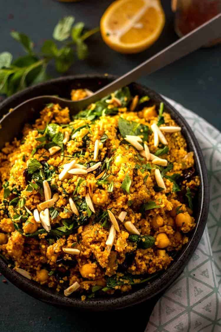 Moroccan Couscous with Chick Peas, Spinach, and Dried Fruit - A close up of the Moroccan couscous in a black bowl.