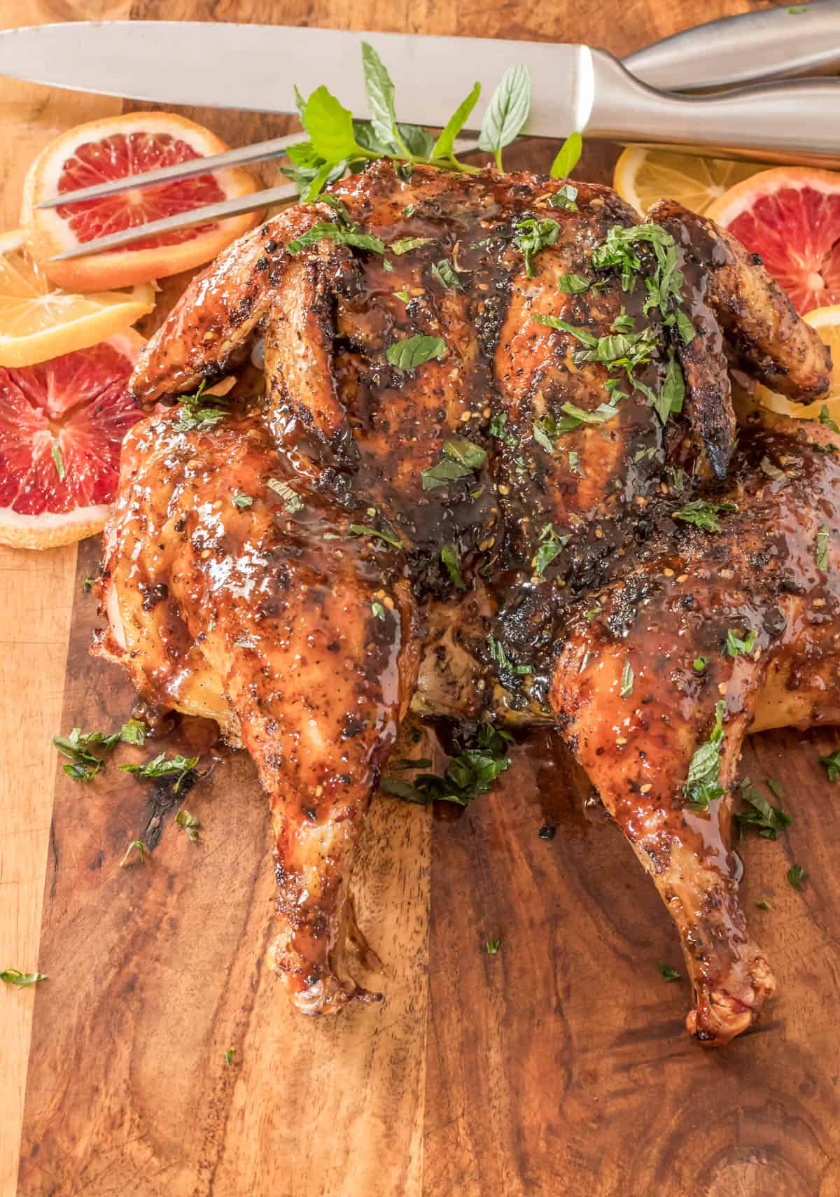 Butterflied and Grilled Za'atar Chicken - the whole chicken on a wood cutting board.