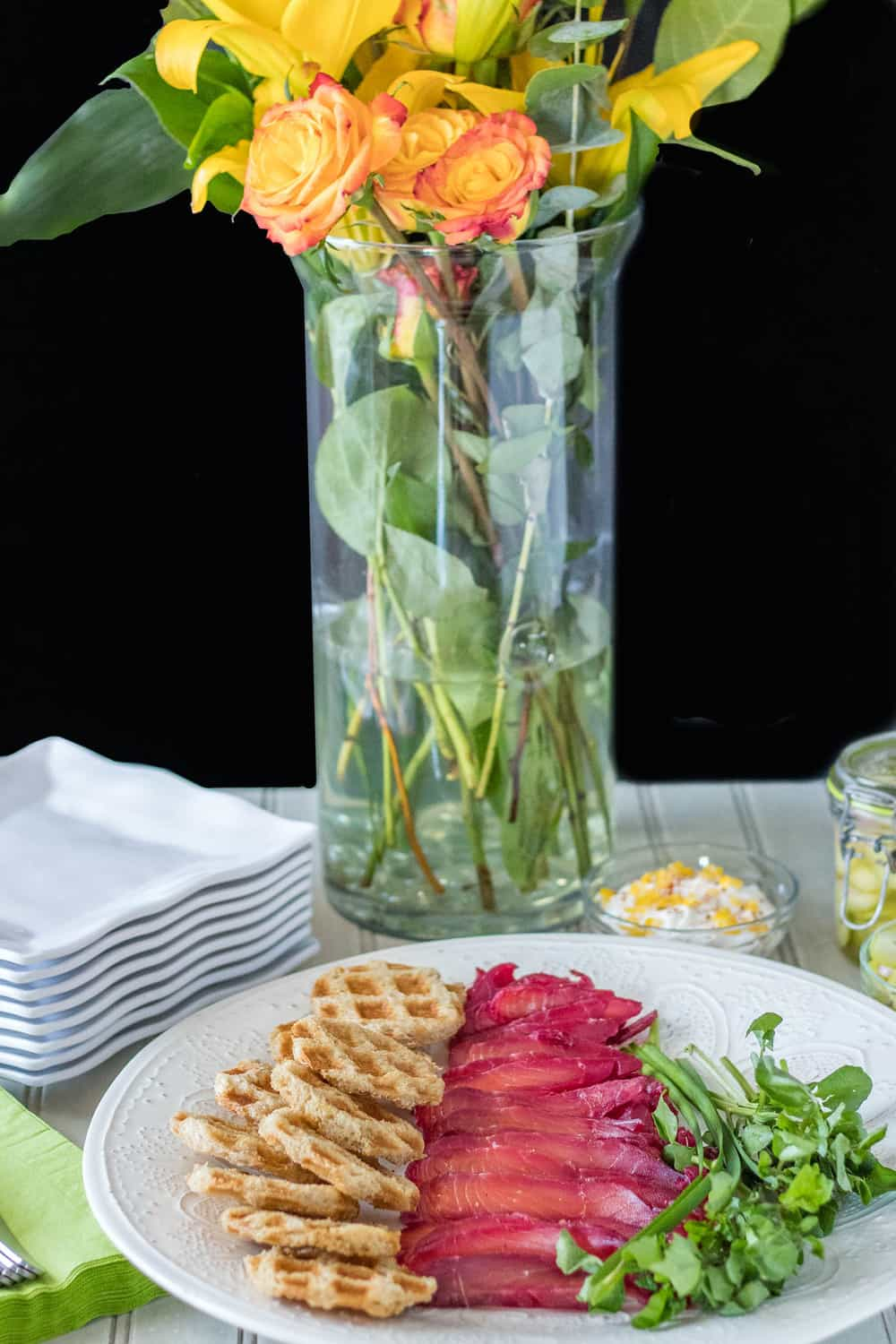 Beet and Gin Cured Salmon Recipe - beet and gin cured salmon with waffle toast and watercress and a vase with fresh flowers in the background.