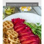 A spring appetizer recipe - Beet and Gin Cured Salmon - on a white platter with toasted rye bread, fresh water cress, pickles, and yogurt.
