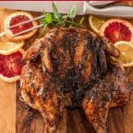 Butterflied and Grilled Za'atar Chicken on a wood cutting board with blood oranges, lemons, mint, and carving tools.