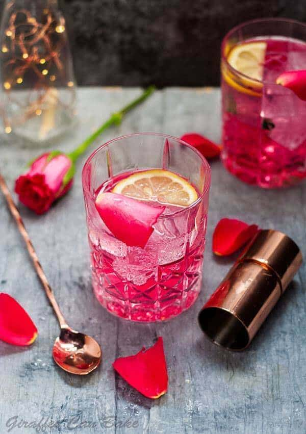 Giraffes Can Bake - a lovely Rose Vodka Tonic with rose petals in a tumbler.