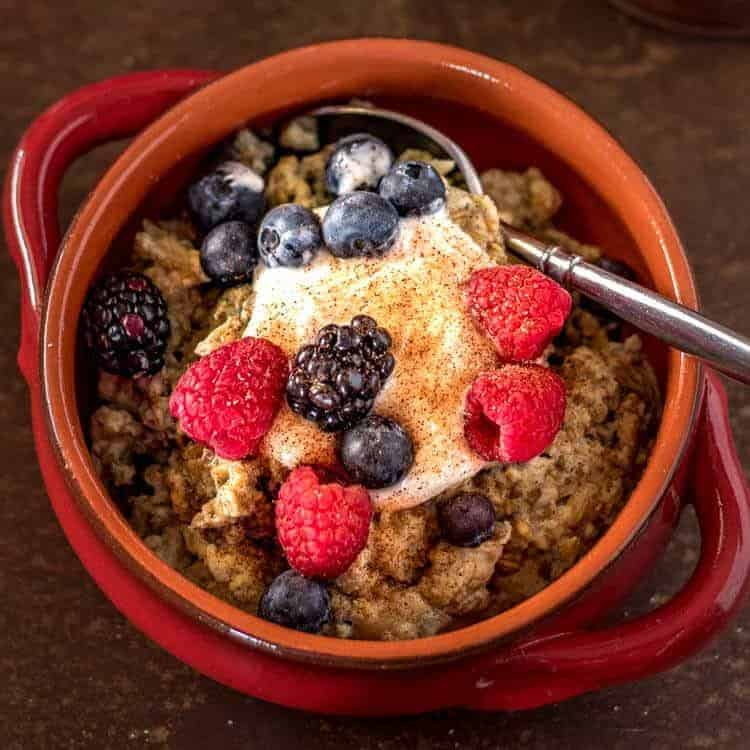 "Instant Pot Breakfast ""Pudding"" - A close up of breakfast pudding, berries, yogurt in a red bowl."