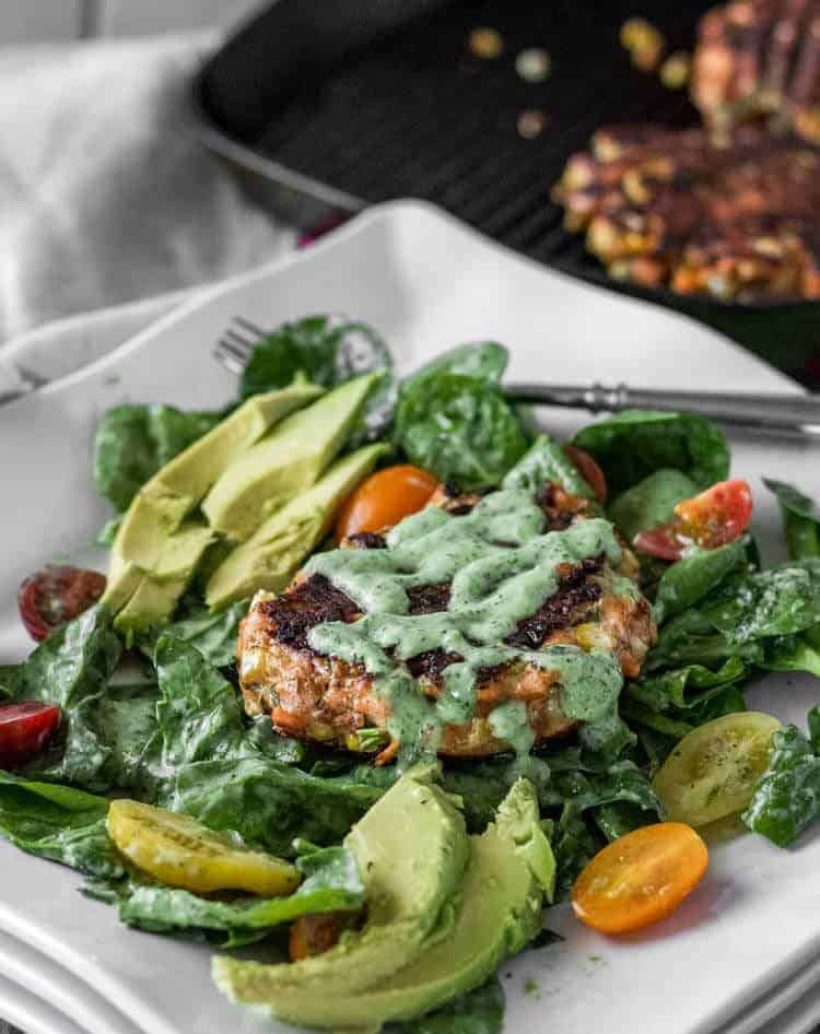 Spicy Mexican Salmon Patties with Creamy Cilantro Ranch and Spinach Salad - a white square plate with a completed Mexican salmon patty atop spinach salad with cilantro ranch dressing.