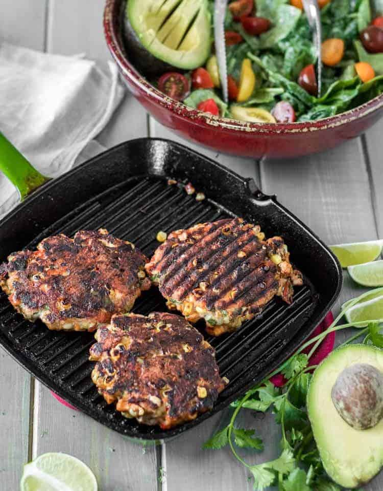 Spicy Mexican Salmon Patties with Creamy Cilantro Ranch and Spinach Salad - 3 salmon patties on a square grill with avocado, lime, and salad.