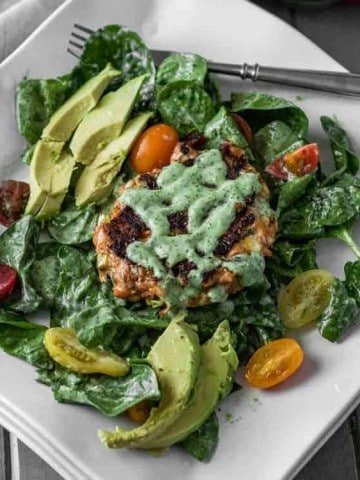 Spicy Mexican Salmon Patties with Creamy Cilantro Ranch and Spinach Salad - a square white plate with completed Mexican Salmon Patty.