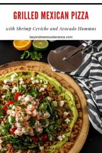 A grilled Mexican pizza spread with avocado hummus, tossed with arugula and tomatoes, and finally, fresh ceviche on a round pizza stone next to a striped napkin.