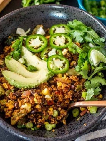 "Low Carb Mexican Cauliflower ""Rice"" Bowls - a square image of a close up in a black bowl of the cauliflower rice."