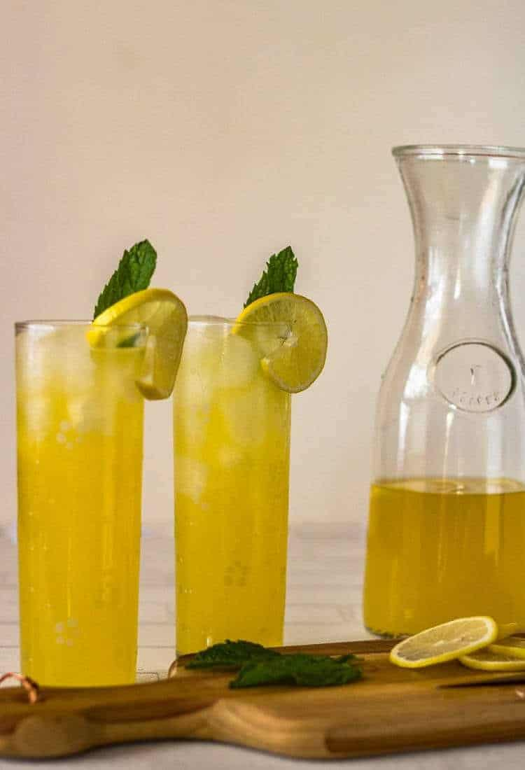 Pisco Lemonade with Lemongrass and Mint - 2 highball glasses with pisco lemonade, and a pitcher.